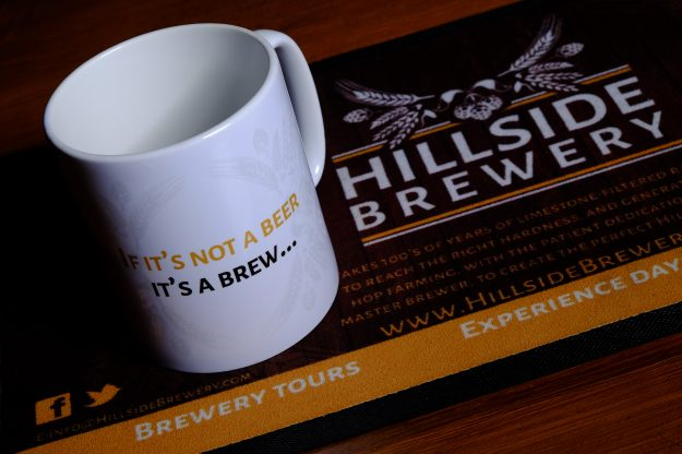 Hillside Brewery branded mugs with slogan.